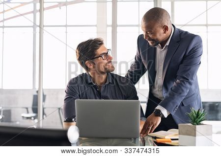 Senior and junior businessman discussing during their meeting. African american executive working with young businessman in modern office. Mature boss with business partner working together on laptop.