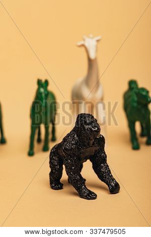 Selective Focus Of Gorilla With Colored Toy Animals On Yellow Background, Extinction Of Animals Conc