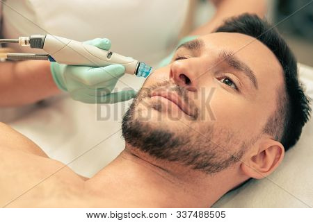 Face Of Bearded Man And Tool For Nourishment Near His Cheek
