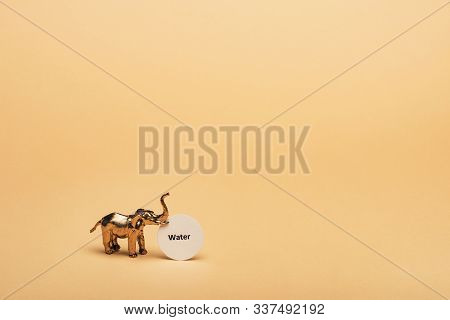 Golden Toy Elephant With Lettering Water On Card On Yellow Background, Water Scarcity Concept