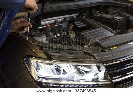 A Mechanic Adjusts The Headlights On A Car. Diode Headlight Of A Modern Car.