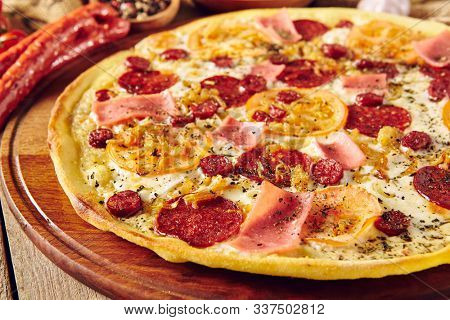 Meat and tomato pizza on wooden table close up. Ham slices, hunter sausages and caramelised onion ingredients on dough composition. Italian takeout dish. Baked snack with salami and cheese