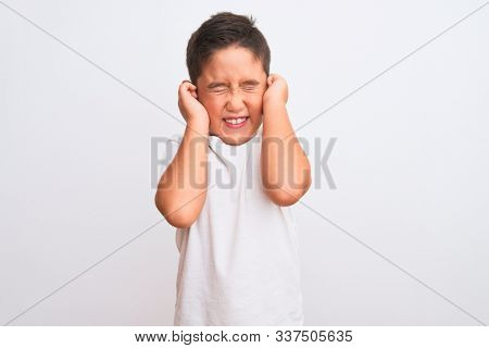 Beautiful kid boy wearing casual t-shirt standing over isolated white background covering ears with fingers with annoyed expression for the noise of loud music. Deaf concept.