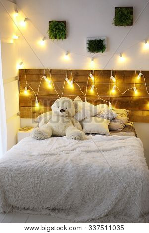 White Bed With Teddy Bear With Christmas Garland Light Decoration Close Up Photo