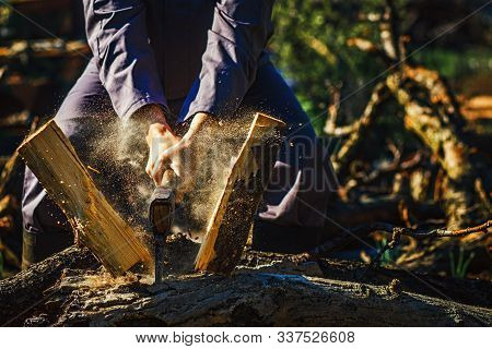 Man Holding An Industrial Ax. Ax In Hand. A Strong Man Holds An Ax In His Hands Against The Backgrou