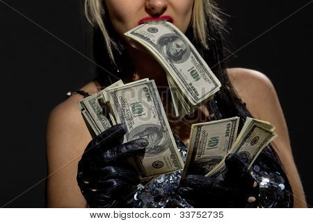 Sexy female with fan of dollars isolated in darkness