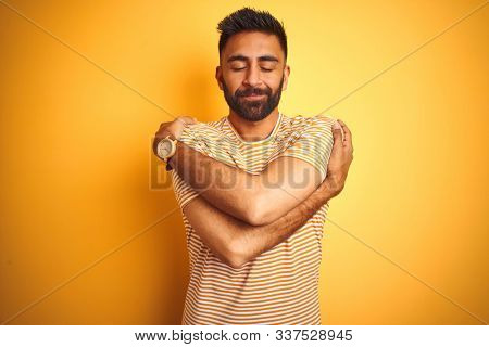 Young indian man wearing t-shirt standing over isolated yellow background Hugging oneself happy and positive, smiling confident. Self love and self care
