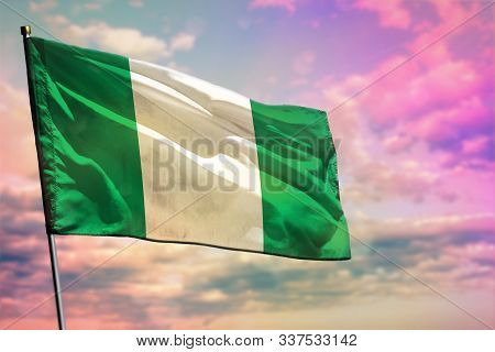 Fluttering Nigeria Flag On Colorful Cloudy Sky Background. Nigeria Prospering Concept.