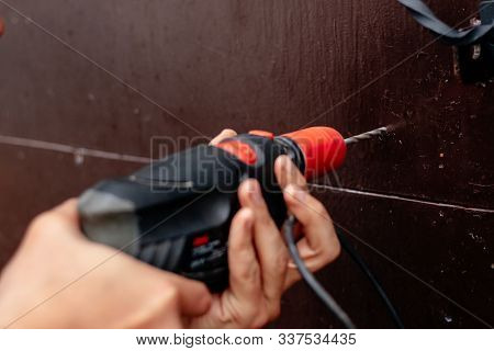 Hands Of A Man Drills With An Electric Drill