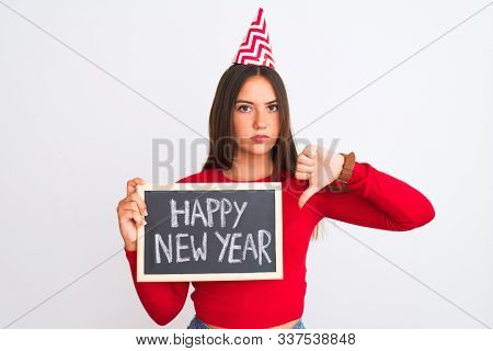 Beautiful girl wearing fanny party hat holding blackboard over isolated white background with angry face, negative sign showing dislike with thumbs down, rejection concept