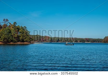 A Man Fishing On Lake Lanier, Georgia In A Motorboat Casting A Line Into The Lake Off The Island Sho