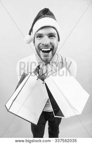 Macho Smile With Shopping Bags On Orange Background. Winter Holidays Celebration. New Year, Xmas Pre
