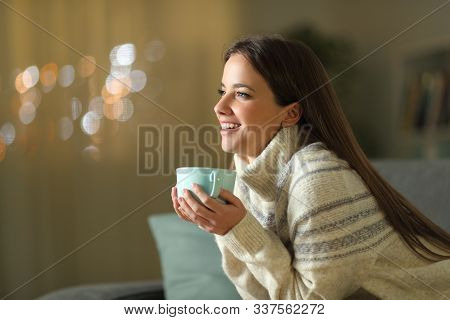 Happy Woman Holding Coffee Cup In Winter Sitting On A Couch In The Living Room At Home In The Night