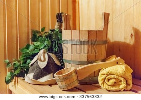 Interior details Finnish sauna steam room with traditional sauna accessories basin birch broom scoop felt hat towel. Traditional old Russian bathhouse SPA Concept. Relax country village bath concept poster