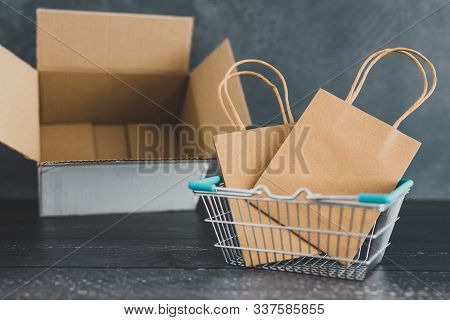 Online Shopping Conceptual Still-life, Parcel And Shopping Basket With Bags Inside