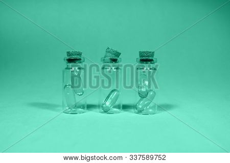 Omega 3, Beneficial Vitamins For Human Health. Capsules Of Fish Oil In Small Glass Jars Lie On A Tab