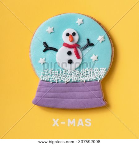 a cookie in the shape of a snow globe, with a snowman inside, and the text x-mas on a yellow background