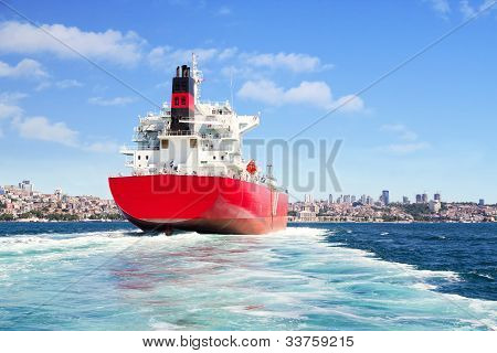 Red cargo ship sailing in to the sea