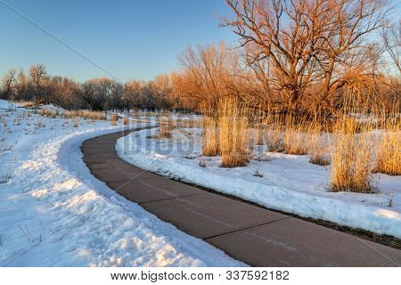 windy bike trail in winter sunset scenery - Poudre River Trail in Fort Collins, Colorado, recreation and commuting concept