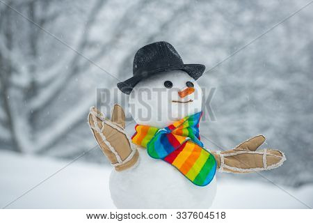 Happy Smiling Snow Man On Sunny Winter Day. Handmade Snowman In The Snow Outdoor. Snowman In A Scarf