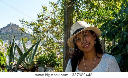 Closeup Of Asian Woman In White T-shirt And Wearing Hat In Athens With Bushes And Lykavetos In The B