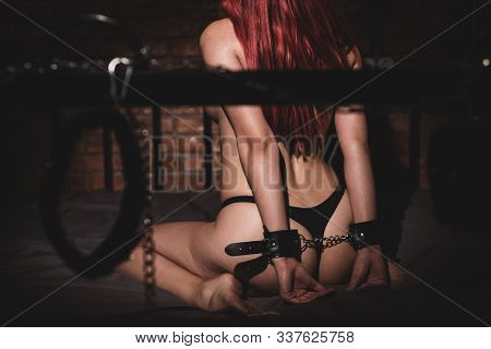 A Woman Sits On A Bed In Leather Handcuffs In Sexual Games As A Victim. Toys For Adults. Bdsm Sexual