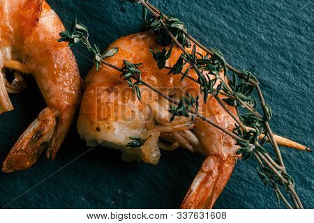 Green Thyme Sprig On The Cooked Headless Prawns