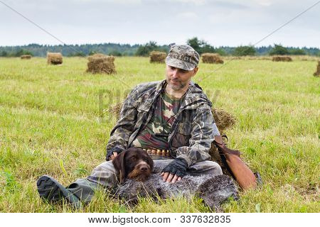 Hunting Dog Resting At The Feet Of The Hunter On The Hayfield During The Autumn Hunting