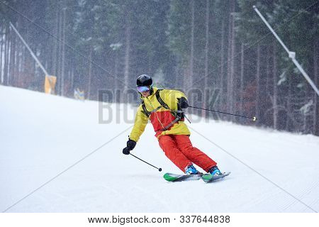 Young Skier Performing Skiing Trick. Ski Training In Dense Snowfall In Mountains. Carving Skiing Tec