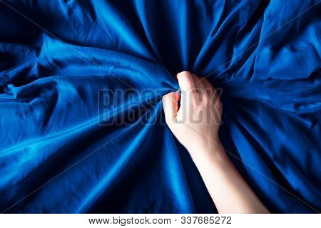 Woman Hand On The Blue Silk Bedding, Sex And Orgasm Concept