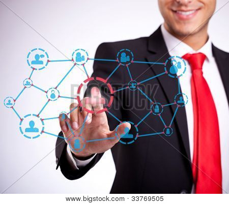 young business man with red tie pressing modern social network buttons on a virtual background and smile