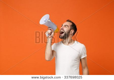 Angry Young Man In Casual White T-shirt Posing Isolated On Bright Orange Wall Background Studio Port