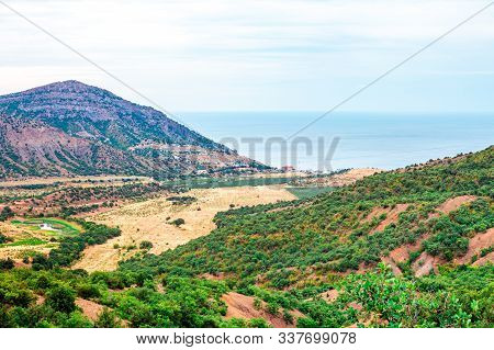 Crimean Mountain Landscape And The Sea Shore In The Distance