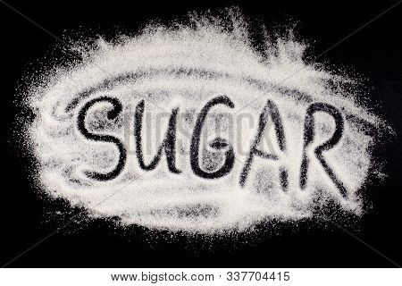 Word Sugar, Hand Lettering On Black Background. The Text Is Written On A Pile Of Powdered White Gran
