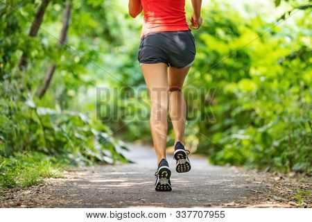 Runner running legs from the back jogging on nature path outside. Running shoes girl training cardio outdoors.