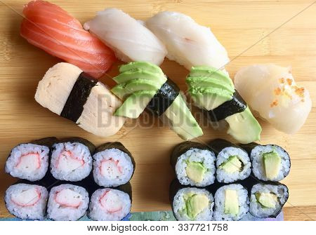 Assorted Sushi And Rolls On A Wood Serving Plate.