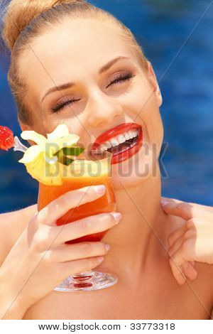 Laughing glamorous blonde woman enjoying a tropical cocktail alongside blue water
