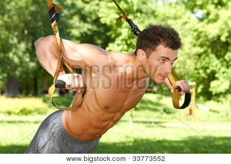 Attractive fittness man doing exercises in park