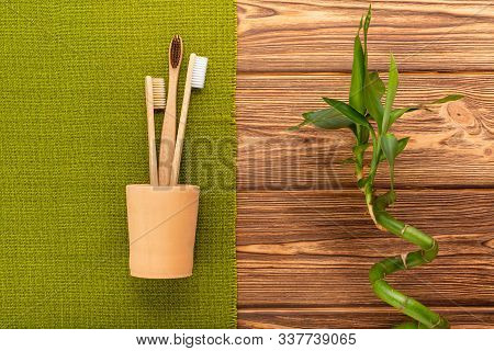 Bamboo Toothbrushes In Hand Made Clay Glass Bamboo Plant With Green Towel On Wooden Background.flat