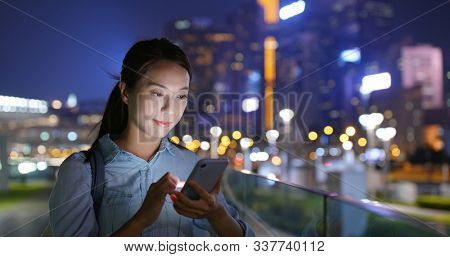 Woman look at cellphone at night in city
