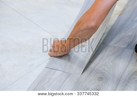 Worker Installing New Vinyl Tile Floor With New Home Improvement Laminate Wood Texture Floor