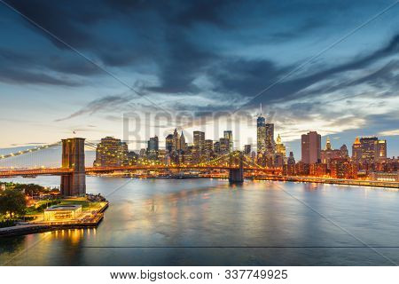 New York, New York, USA downtown Manhattan city skyline over the East River with the Brooklyn Bridge at dusk.