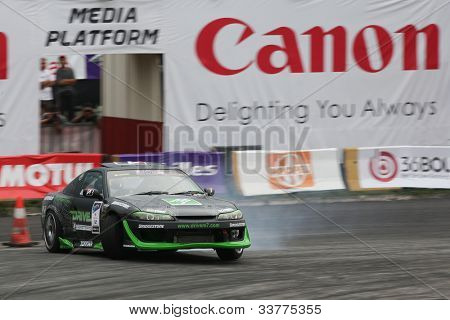 KUALA LUMPUR - MAY 20: Malaysia's Tengku Djan power slides into a turn during the Formula Drift 2012 Asia Round 1 on May 20, 2012 in Speedcity, Malaysia. Tengku Djan won third place in this event.