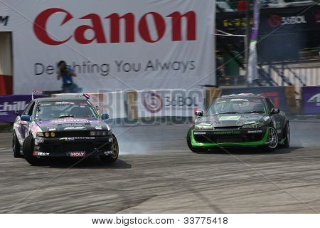 KUALA LUMPUR - MAY 20: Tengku Djan (right) chases Ser Ming Hui (left) at the Formula Drift 2012 Asia Round 1 on May 20, 2012 in Speedcity, Malaysia. Tengku Djan won third place in this tournament.