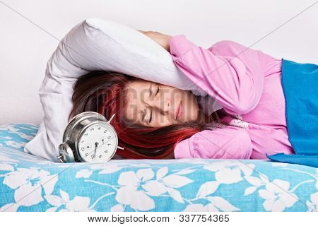 Annoyed Girl Covering Her Ears With A Pillow From The Alarm Clock
