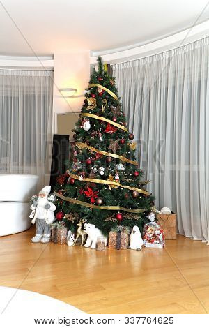 Tall Decorative Christmas Tree In Modern Room With Gifts Underneath