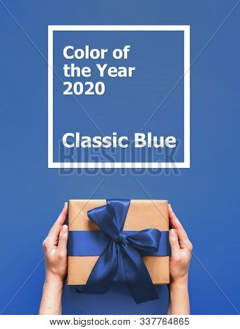 Female Hands Hold Gift Box On Blue Background With Words Color Of The Year 2020 Classic Blue. Gift B