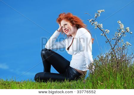 Outdoor portrait of beautiful readheaded girl resting on grass over blue sky at spring