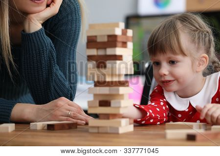Portrait Of Interested Girl Having Happy Time With Mother. Smiling Interested Child Playing Educatio