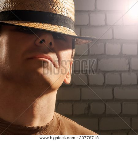 Selfconfident man wearing hat with brick wall in the background